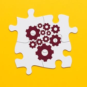 Roue dentée marron sur puzzle blanc connecté sur une surface jaune