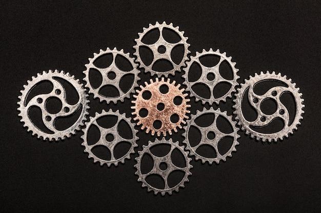 Roue dentée en or rose entourée de roues dentées en métal