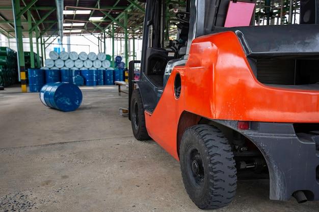 La roue du chariot élévateur soulève des barils de pétrole des barils chimiques bleus barils chimiques empilés horizontalement