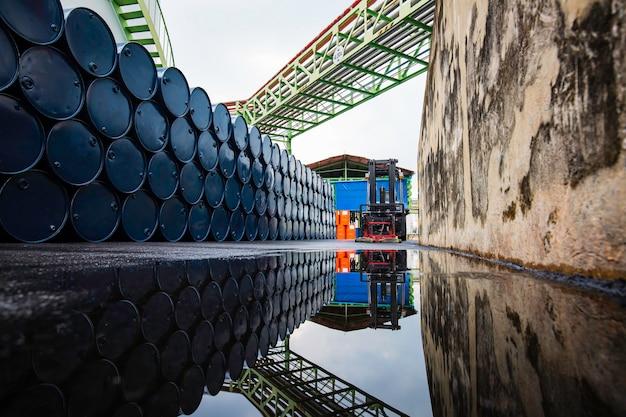 La roue du chariot élévateur soulève des barils de produits chimiques barils de pétrole bleus barils chimiques réservoir empilé horizontal réflexion eau.
