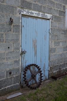 Roue de garniture en acier vintage devant une porte de grange antique bleue en saskatchewan, canada