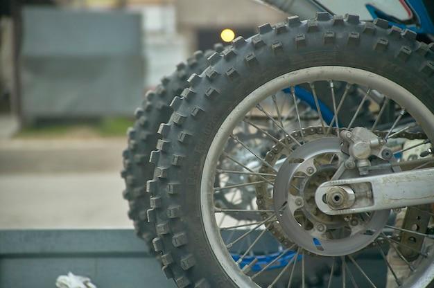 Roue de moto cross (ou enduro) avec pneus non goudronnés pour une meilleure traction sur terrain difficile.