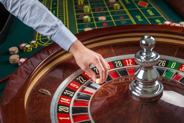 Roue de roulette et main de croupier avec boule blanche au casino