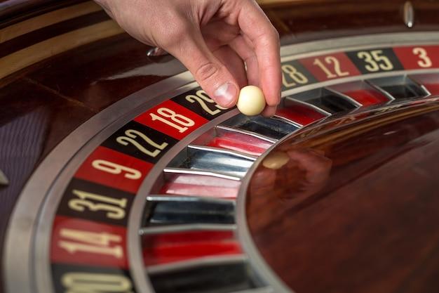 Roue de roulette et main de croupier avec boule blanche dans les détails de gros plan du casino