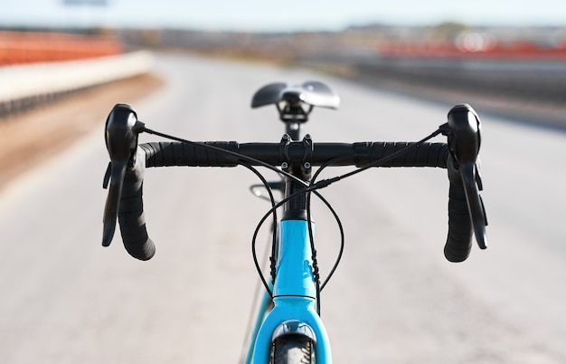 La roue d'un vélo de sport avec le gros plan des poignées de frein et du levier de vitesses.