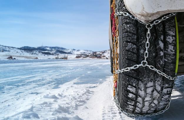 Roue d'une voiture avec des chaînes sur la neige