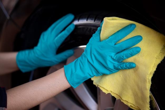 Roue de voiture de nettoyage avec des gants verts et un chiffon en fibre jaune se bouchent