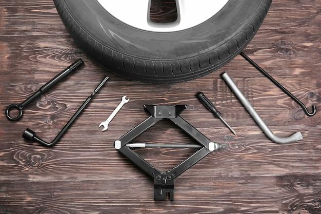 Roue de voiture avec des outils sur fond de bois