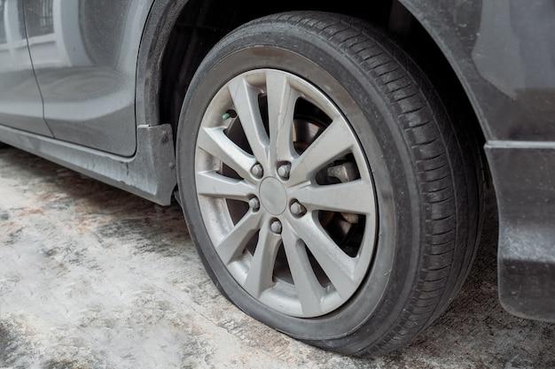 Roue de voiture avec pneu à plat et fuite d'air due à un accident.