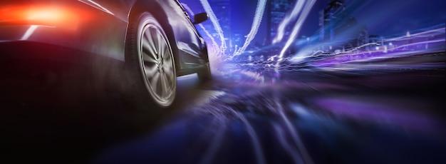 Roue de voiture de sport à la dérive sur fond d'éclairage de nuit de la ville