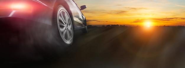 Roue de voiture de sport à la dérive et fumée au lever du soleil