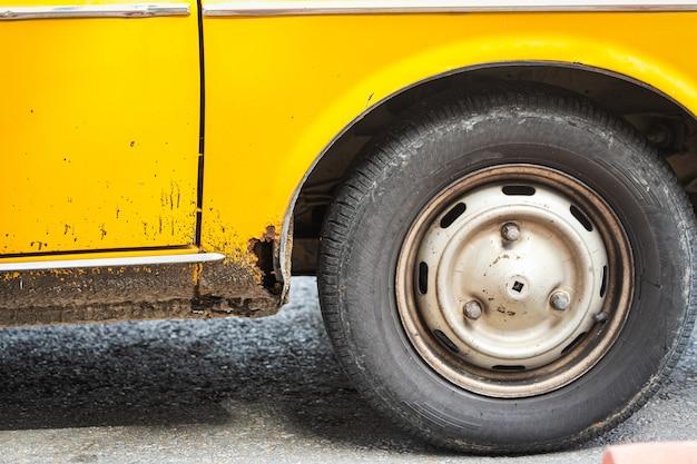 Roue de voiture sur une vieille voiture rouillée jaune