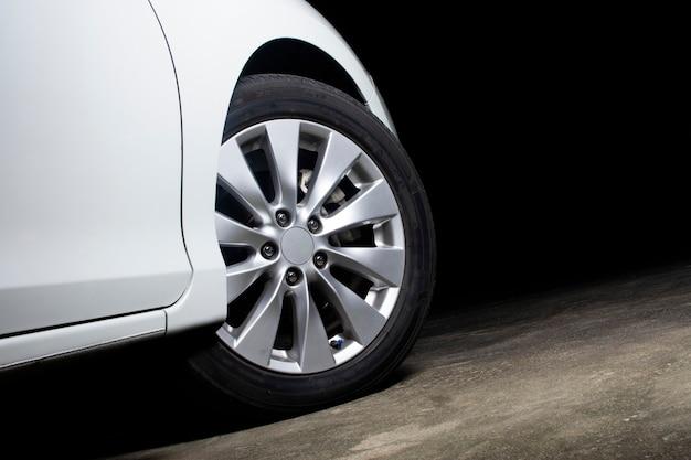Les roues en alliage d'une voiture blanche tournent sur la route en ciment du parking avec copie espace