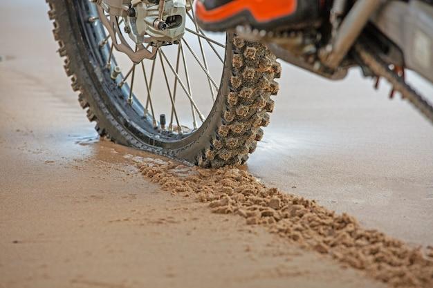 Les roues de moto laissent des traces de pas dans le sable mouillé sur la plage