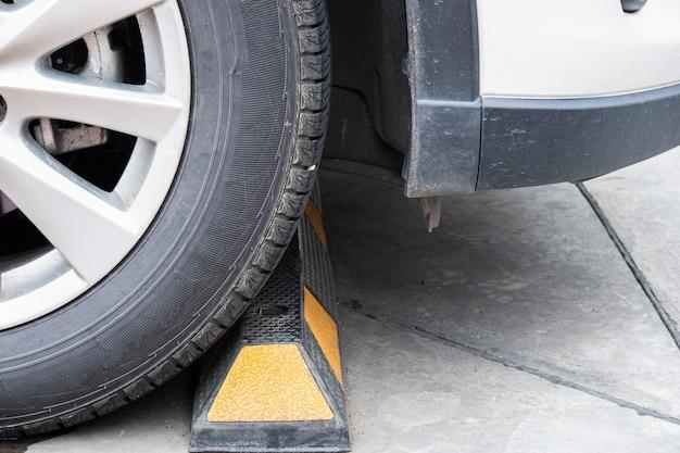 Les roues de la voiture sont bloquées par des tiges de ciment dans le parking