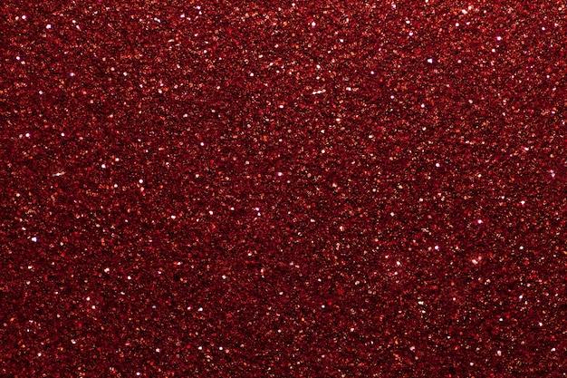 Rouge foncé mousseux petits paillettes, gros plan. toile de fond brillante.