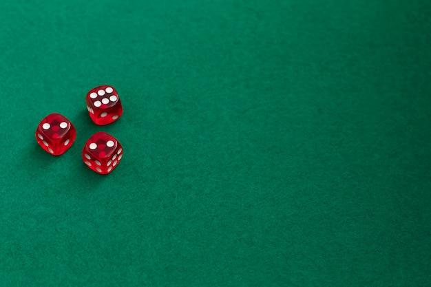 Dés rouge sur fond vert et noir.