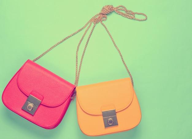 Rouge et jaune deux sacs en cuir avec chaîne sur fond jaune. concept de mode de minimalisme. vue de dessus