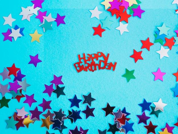 Rouge joyeux anniversaire et différentes confettis d'étoiles