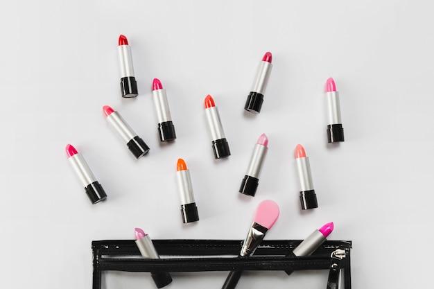 Rouge à lèvres et applicateur près du sac à maquillage
