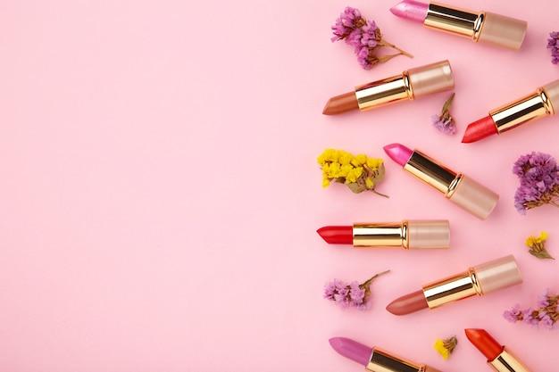 Rouge à lèvres avec de belles fleurs sur fond rose avec espace copie