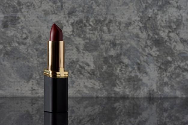 Rouge à lèvres couleur vin avec du noir sur une surface en marbre avec un fond blanc avec du gris
