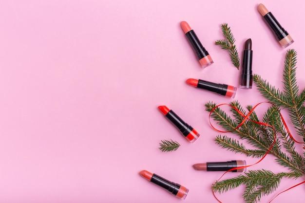 Rouge à lèvres et décoration de noël sur fond rose