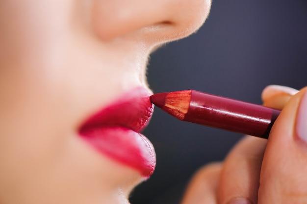 Rouge à lèvres. gros plan du visage de femme avec rouge à lèvres mat rouge vif sur les lèvres pleines. cosmétiques de beauté, concept de maquillage. image haute résolution.