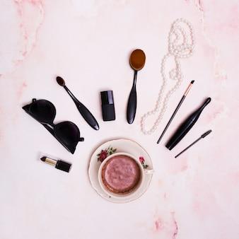 Rouge à lèvres noir; des lunettes de soleil; pinceau de maquillage; mascara; collier de perles blanches et une bouteille de vernis à ongles sur la tasse à café en céramique