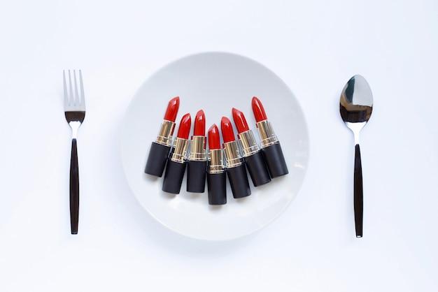 Rouge à lèvres sur plat blanc avec fourchette et cuillère sur blanc