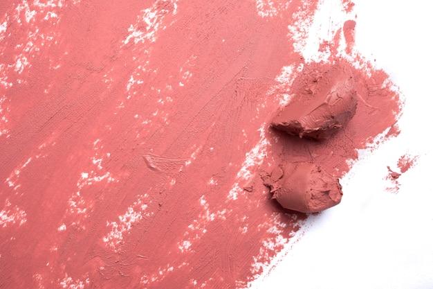Rouge à lèvres rose taché sur fond blanc.