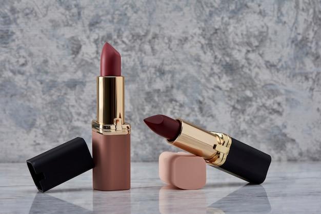 Rouge à lèvres rouge avec du noir et du rose sur une surface en marbre avec les capuchons jetés sur le côté