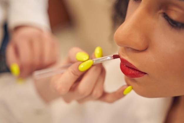 Le rouge à lèvres rouge est soigneusement appliqué par un visagiste qualifié à l'aide d'un pinceau à lèvres professionnel