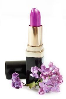 Rouge à lèvres violet et fleurs lilas sur fond blanc