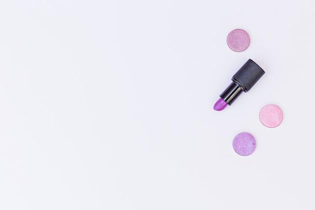 Rouge à lèvres violet et ombre à paupières sur fond blanc