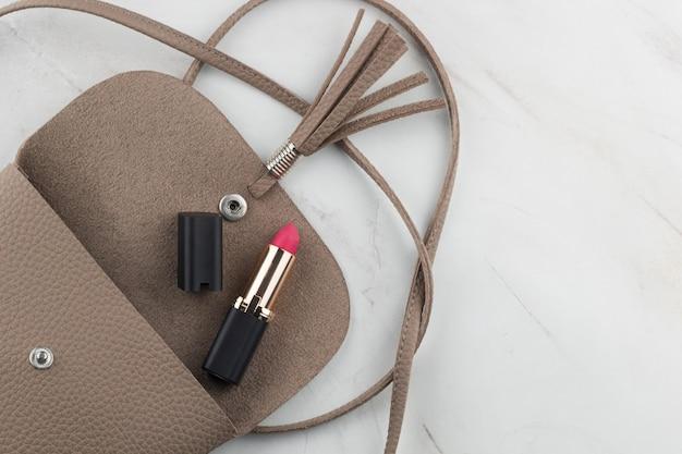 Rouge à lèvres vue de dessus dans un sac ouvert sur la table de marbre