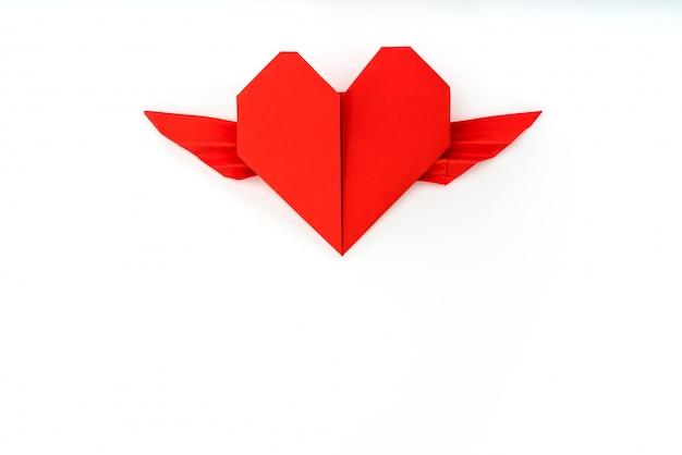 Rouge papier origami coeur avec des ailes sur fond blanc.