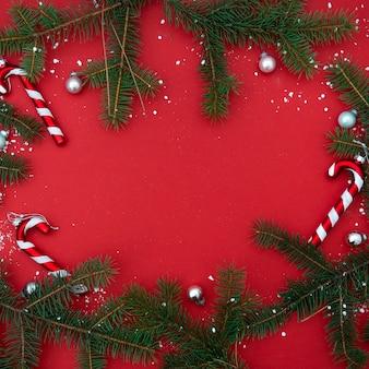 Rouge plat poser bannière carrée de noël minimaliste avec des branches de sapin et des bonbons, arbre de noël et jouets.