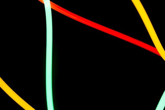 Rouge; tubes de néon jaune et vert sur fond noir