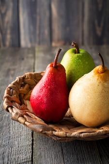 Rouge, vert, jaune, poire douce et une pomme sur une assiette en rotin sur un fond sombre