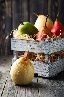 Rouge, vert, jaune, poire douce et une pomme dans la vieille boîte en bois sur une sombre