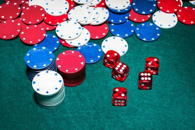 Des dés rouges et des jetons de casino sur une table de poker verte