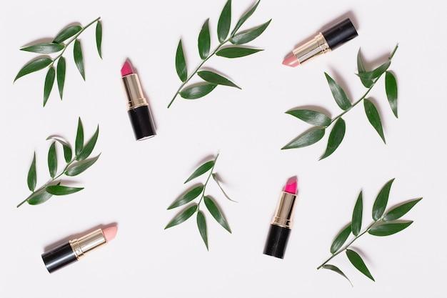 Rouges à lèvres et branches de plantes sur blanc