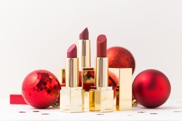 Rouges à lèvres dans un étui en or et boules de noël rouges.