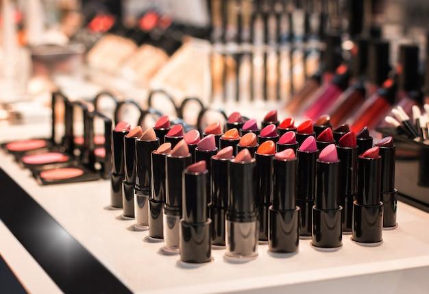 Rouges à lèvres de différentes couleurs à un comptoir dans le magasin de cosmétiques échantillons de test vue de face