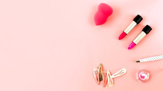 Rouges à lèvres et éponge près des épingles à cheveux