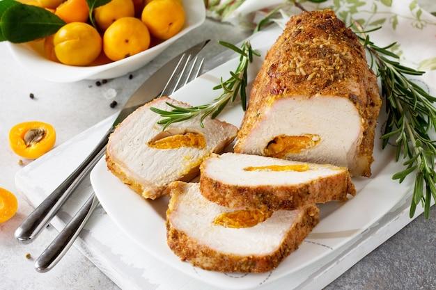 Roulade de rouleau de viande avec farce aux abricots et épices sur fond de pierre claire ou d'ardoise