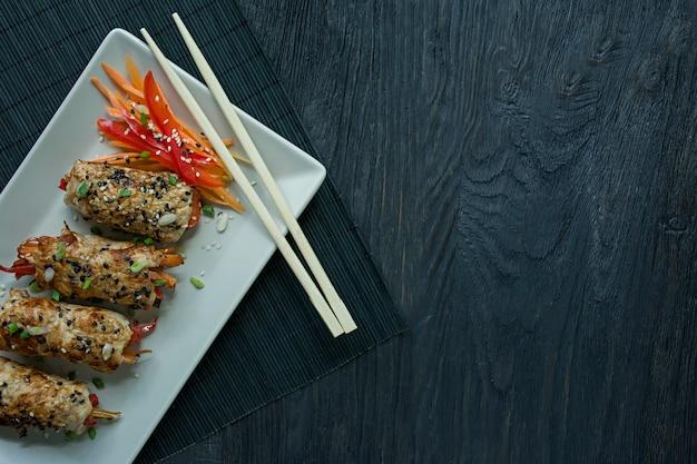 Roulades de poitrine de poulet faites maison avec des légumes verts, des tranches de carotte et du poivron sur une assiette rectangulaire légère.
