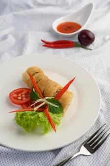 Rouleau aux œufs ou rouleaux de printemps frits sur la plaque blanche de la nourriture thaïlandaise. .