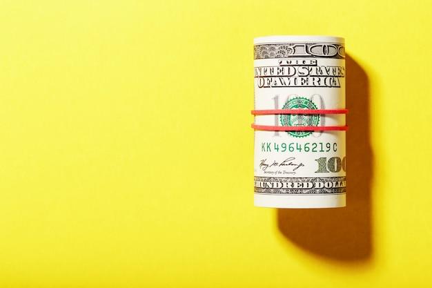 Un rouleau de billets de cent dollars américains est attaché avec une bande élastique rouge sur fond jaune.